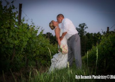 Couple Kissing Among Vines Outside Winery
