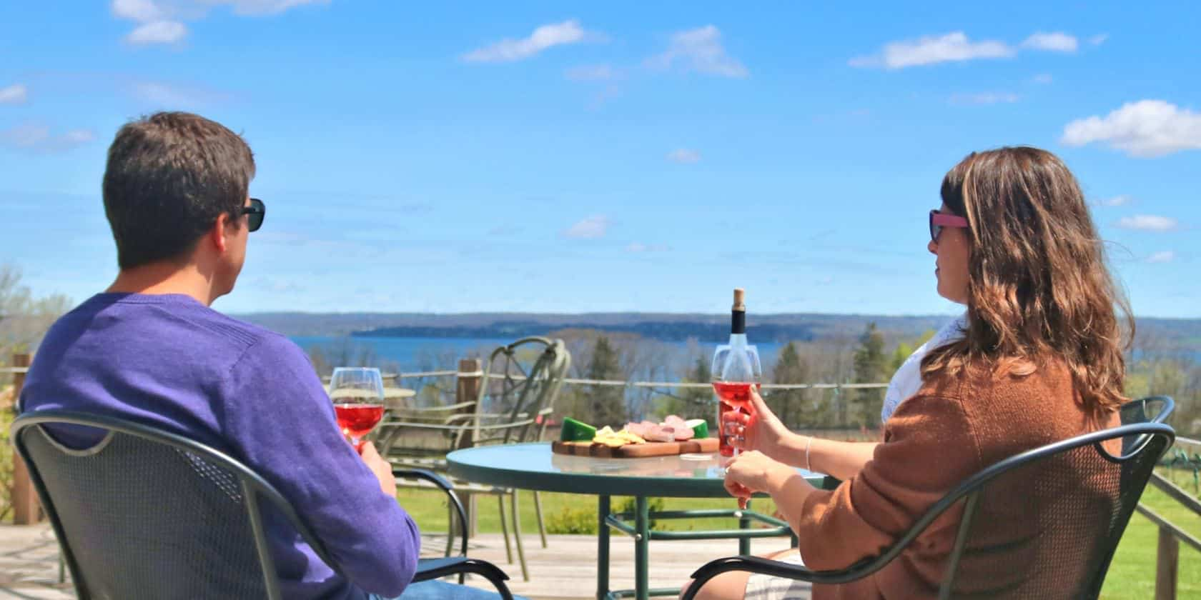 2 People Overlooking Buttonwood Grove View Vineyards Drinking Rose Wine