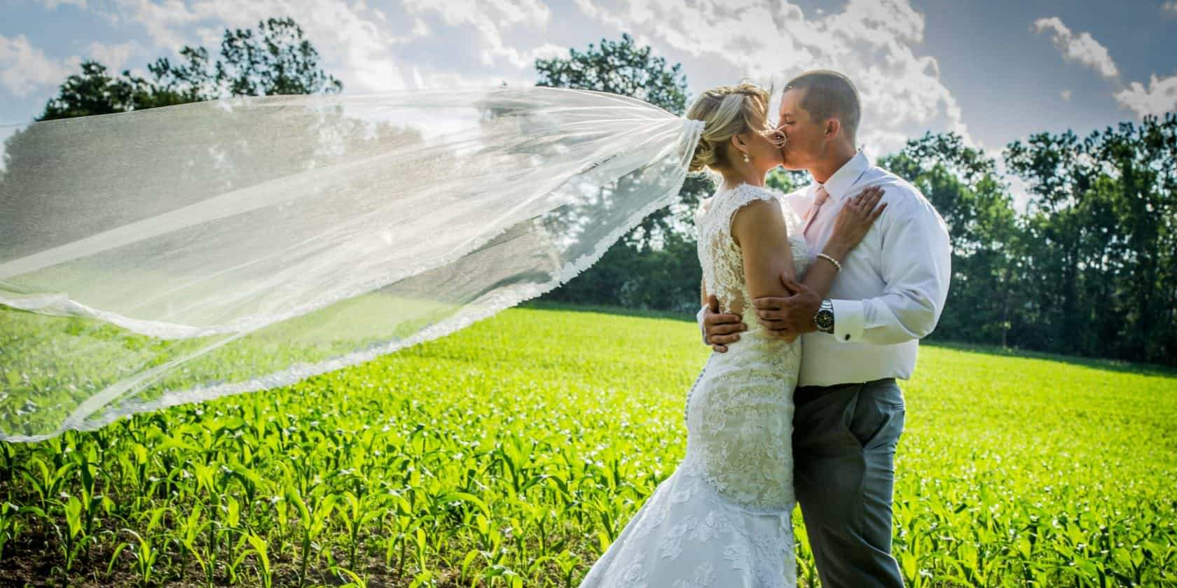 Buttonwood Grove Wedding Couple Kissing with Veil Blowing in the Wind